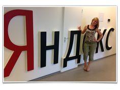 Менеджер по работе с клиентами Катя Фатеева на фоне логотипа Яндекс в центральном офисе компании в СПБ на встрече партнеров.