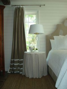 Love the drapes, the round table, the shape of the headboard... oh and the beadboard wall!