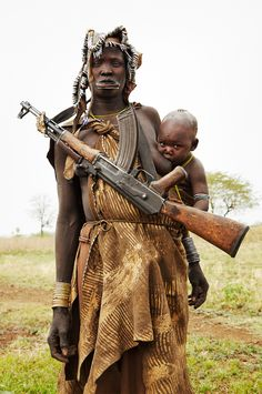 This is Africa, Our Africa : this is the definition of thought provoking. Mursi Mother with Protection, Ethiopia.
