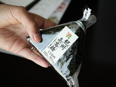 Nori wrapped rice ball inside a plastic sleeve.
