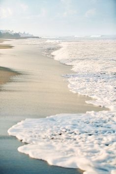 Seafoam waves on the shoreline at the beach by the ocean under a blue sky on a…