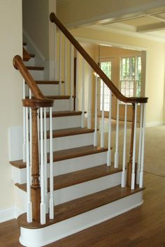 Oak stairs with white riser and spindles.  Ours are square and the risers are carpeted.  Now up to code and the grandbabies can't walk through the spindles now !