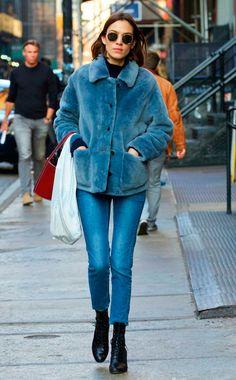 Alexa Chung posa para foto de street style usando turtleneck preta, óculos ray-ban redondo, casaco faux fur azul, calça jeans skinny azul, botas coturno preto