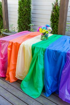 Use multiple plastic table cloths to create an easy rainbow party table!