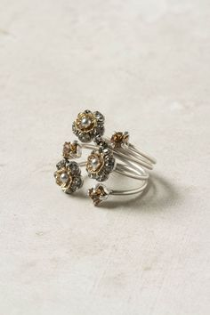 """A patch of petals sits tall on this set of four bronzed rings by Eric et Lydie. - Set of four rings - Adjustable - Bronze plated brass, 14k gold, plastic, glass - 0.5""""W - Handmade in France"""