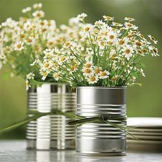 cute to pair tin cans with mason jars and brown or green glass beer bottles with wildflowers on a farmhouse table