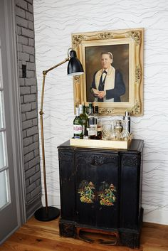 Make a Big statement with art. via How To Make Your Place Look AWESOME #refinery29  http://www.refinery29.com/ideas-for-small-space-living#slide10  Honor a meaningful piece.   Using an old portrait of Abby's father, and a hand-me down cabinet, we were able to create a really interesting bar nook. We added a new drinks tray and floor lamp for height and shine.
