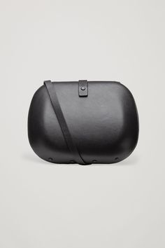 092d08bf0f1 This hard case shoulder bag is made from soft leather with a matte finish.  A minimal design, it has a single lined main compartment, a small inside  pocket ...