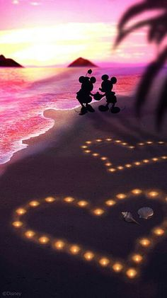 Mickey & Minnie having fun on the beach as the sun sets.