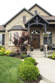 Love everything about this exterior! Love the beams, the stone, the exterior paint, the railing, the metal roof, the seating area, and the landscaping.