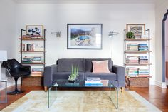 """The bookshelves that flank the sofa are Helix Acacia from CB2, and the art above the sofa is a print of """"Poolside Glamour"""" by Slim Aarons."""
