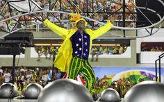 Integrante da Mocidade vestido com as cores da bandeira do Brasil dança em carro alegórico