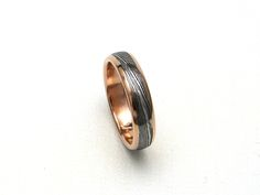 http://www.jloose.com/siteimages/redgoldrails2.jpg Men's wedding band, a handmade, sole-authored stainless damascus ring in 14K rose / red gold with rails.