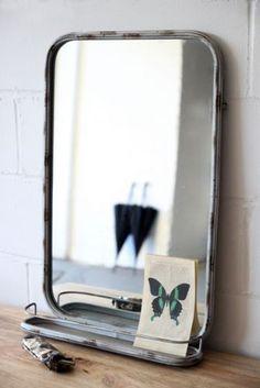 Aged wall mirror with shelf.