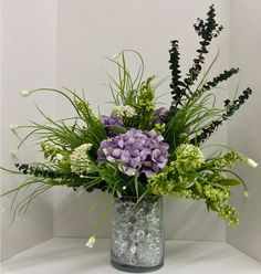 Spring 2015 Contemporary Floral: Violet hydrangeas, Queen Ann bush, rose narr bush, Eva astible, eucalyptus and lustre clear marbles on cylinder glass vase. Original design and arrangement by http://nfmdesign.synthasite.com/