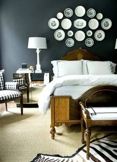 Displaying plate collections is centuries old, what is new are their locations. No longer is the dining room or kitchen the only way to go. Case point, white ironstone and black transferware above a headboard. They contrast nicely with the bedroom's charcoal walls. Crisp hotel-style linens, a zebra rug and gingham chair repeat their colors.