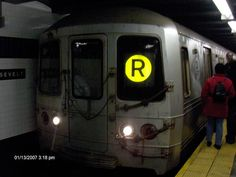 An R46 R train at Roosevelt Avenue.  The R Broadway Local is a rapid transit service in the B Division of the New York City Subway.  It is colored sunflower yellow on route signs, on station signs, and on the official subway map, because it runs on the BMT Broadway Line in Manhattan.