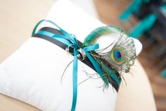 DIY ring bearer pillow.   Washed a goodwill pillow, add ribbon and peacock feathers
