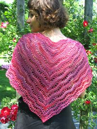 """More than a """"mere bagatelle"""", this piece plays with a lacy stitch pattern and strategically placed short rows to create a playful summer shawl.  Increases at the centre and short rows insinuate a curving shape that results in a shawl that will sit comfortably on your shoulders. The ties at each end allow you to wrap and tie as you like.  The sample pictured is knit with Fleece Artist Sea Wool, 70% merino, wool, 30% sea cell, (350 m./383 yds. per 112 g. skein), colour """"Valentine"""