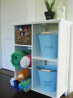 organizing a shelf for summer - do this in the garage!  She wrote on the pails with dry erase marker.