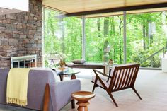 The family room is surrounded by large, floor-to-ceiling windows. The furniture is vintage midcentury modern pieces.