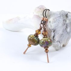 These artisan lampwork earrings feature handmade lampwork beads, copper paddle wires, Bali style spacers, Swarovski crystals and niobium French ear wires.