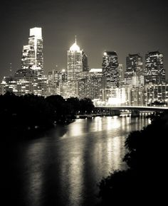 Philadelphia Skyline. I love how the black and white here brings out the lighting of the city at night. While you can't see a direct mirror effect on the water, you can see how the water brightens up the rest of the picture because they catch the lights of the city.