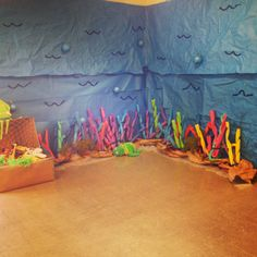 Our underwater corner! We used blue crumpled bulletin board paper as the water with blue painters tape to make the waves/ripples. Then made a treasure chest out of a cardboard box. Added cut up pool noodles as coral!