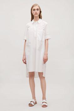 This shirt dress is made from a crisp cotton poplin with simple topstitch finished details. A voluminous A-line shape and fit, it has casual in-seam pockets, a button half-placket and a straight hemline that is longer at the back.