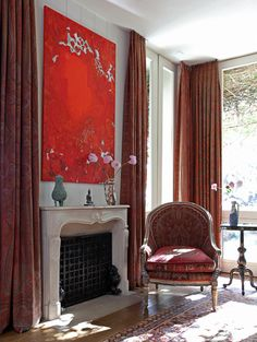 Incredible floor to ceiling red paisley curtains! Exotic looking upholstered red chair.