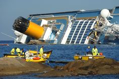 The cruise ship Costa Concordia lies stricken off the shore of the island of Giglio as floating barriers are positioned to prevent pollution of the coasts on Jan. 18, 2012 in Giglio Porto, Italy. The official death toll is now 11, with some twenty people still missing. The rescue operation was temporarily suspended earlier due to the ship  moving as it slowly sinks further into the sea.