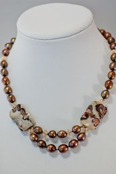 Gorgeous silky, coppery bronze 10mm potatoe pearls are hand knotted onto a silk strand. These pearls are some of the finest to be found. Two feature beads of Crazy Horse Jasper accent the necklace str
