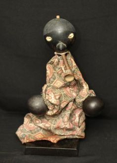HAND PUPPET WITH PIPE. Ghana. The head and hands are small calabash gourds and the eyes are cowrie shells.
