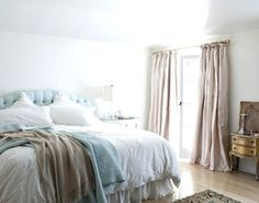 In love with the airy and cozy feel of this bedroom - especially the blue tufted headboard!