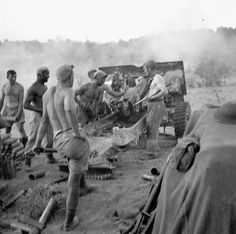 """Gunners of the 7th Battery, 2nd Field Regiment, Royal Canadian Artillery (R.C.A.), firing their 25-pounder guns at German positions, Nissoria, Italy, 23-28 July 1943. Photographer Lieut. """"Big"""" Jack H. Smith. DND PA-177113, LAC MIKAN 3259922."""