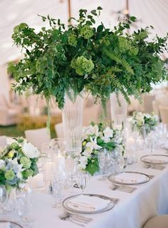 For a fresh, clean look - tall, green centerpieces on tables of white linen and glass plates ~ http://www.stylemepretty.com/2016/02/10/trending-high-centerpieces-thatll-wow-your-guests/: