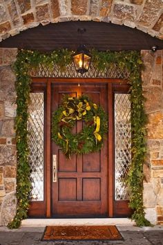 A simple lighted garland embellishes the outer edge of leaded glass panels that frame the front door. - Traditional Home ® / Photo: John Bessler / Design: Lucy Earl #Horchowholidays14