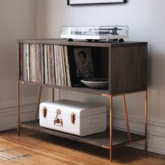 record holder. Literally, because it's designed to hold LPs. Figuratively, because it's possibly the best looking console in the biz. Sleek and architectural, rich mango wood sits on shiny copper legs that are all rock and roll. Designed by Zak Rose to have more than just looks, console opens a cubby for record storage and a lower shelf for overflow. Pop the turntable on top and you're ready to party. Tip: Also works wonders as a console in the entry or anywhere you need a little extra…