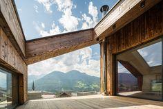 Die Fassadengestaltung des Einfamilienhauses zeichnet sich durch die Ausrichtung der Fenster aus, welche an die Ausblicke auf die umliegende Berglandschaft angepasst ist. Das Haus spiegelt dadurch eine Transparenz wieder, was der Idee eines offenen Lebensstils und einem gefühlvollen Umgang mit der Natur nahekommt. Im Herzen des Hauses werden alle Stockwerke durch eine offene Deckenkonstruktion miteinander verbunden, was im Innenraum ein Atrium entstehen lässt. Atrium, Windows, Architecture, House, See Through, Home, Room Interior, Mountain Landscape, Detached House