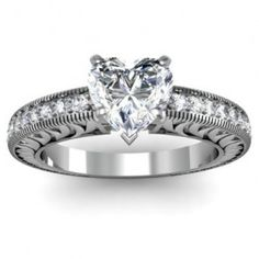 Vintage Diamond Heart Engagement Ring - Here's a splendid Vintage Diamond Heart Engagement Ring that features a 2 carat Heart Shaped gemstone in a Pave setting. This GIA certified diamond ring is flanked with 16 pristine White Round Brilliant cut accent stones. The diamonds are G in color quality, I1 in diamond clarity & also stamped in a 14k White Gold. The total gem weight of the ring is 2.20 carats & all of the diamonds are 100% natural. #unusualengagementrings