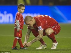 Skrtel senior bends down to tie his son's shoelaces ahead of the victory against Tottenham