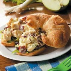 CURRIED CHICKEN SALAD: 2 cups cubed cooked chicken breast 3/4 cup chopped apple 3/4 cup dried cranberries 3/4 cup mayonnaise 1/2 cup chopped walnuts 1/2 cup chopped celery 2 teaspoons lemon juice 1 tablespoon chopped green onion 1 teaspoon curry powder 6 lettuce leaves 6 croissants, split