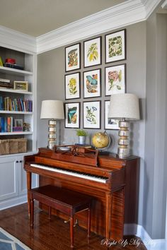 Here is a piano like yours. Two lamps and the series of prints above give it design pizazz. For your wall, the series of prints could go higher with your TV as the central element (see blue coral prints that would look great surrounding a flat screen. Blue bench seat would pull it together.