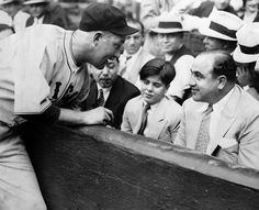 Cubs catcher Gabby Hartnett signing a baseball for Sonny Capone, the son of Al Capone. [1931]