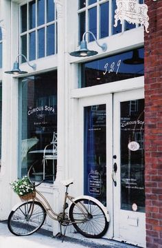A very chic white shop front, white bike, white flowers!