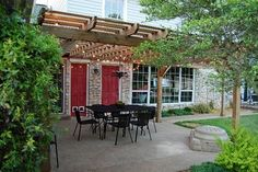 LOVE this outdoor space...the pergola, the lights, the red doors....ALL of it.