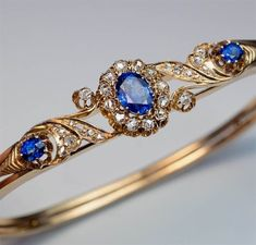 Antique Victorian Era Sapphire Diamond Gold Bracelet, Moscow, circa 1890. A 14K gold bangle bracelet is centered with a sparkling blue sapphire surrounded by old rose cut diamonds, flanked by two diamond-set scrolls and two smaller sapphires. #VintageJewelry