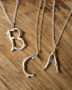 A silver monogram pendant has an appealingly rustic charm.