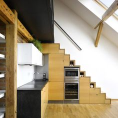 Mezzanine level for micro house with kitchen appliances in stairway.