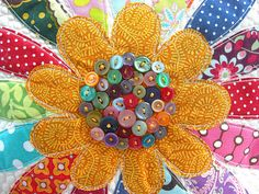 quilted flower in bright cheery patterns with colorful buttons in the center